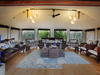 Pelo Camp, spacious comfortable indoor lounge area, large blue throw rug, blue horns, windows encircling the entirety of the room, Africa, Botswana