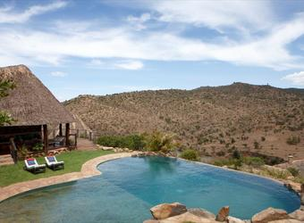 Borana Lodge, absolutely gorgeous central infinity pool overlooking the surrounding mountains complete with lounge chairs for sunbathing in Kenya