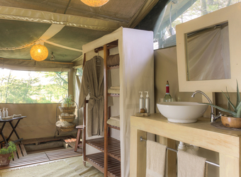 Kicheche Bush Camp, safari crew member sets the places at the dining table in a secluded enclosed safari tent in Kenya, Africa luxury safaris