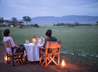 Little Governor's Camp, the beautiful hues of the African landscape are brought out as a roaring fire is surrounded by safari chairs in Kenya