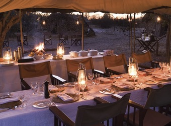 Chobe Under Canvas, open air outdoor covered dining area, beautifully lit tables with luxury dining experience, sunset in Africa, Botswana