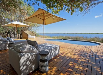 Duma Tau Camp, central crystal clear pool, surrounded by gargantuan sun deck with reclinging chairs and accompanying umbrella, Botswana, Africa safari