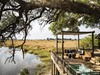 Kings Pool Camp, central infinity pool overlooking lagoon, comfotable couch on main deck area, beautiful natural lagoon, Botswana, Africa safari