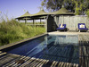 Little Vumbura Camp, pristene blue central pool, sundeck with accompanying reclining seats, large tufts of light green grasses, Botswana, Africa