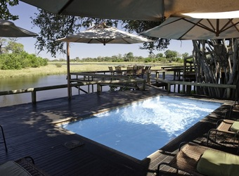 Savuti, pristene inviting swimming pool overlooking a secluded watering hole for animals, expansive deck and sunning chairs for wildlife viewing