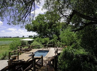 Tobu Tree Camp, inviting pool encircled by protective railing and sundeck overlooking large expanse of African wilderness in Botswana,Africa safaris
