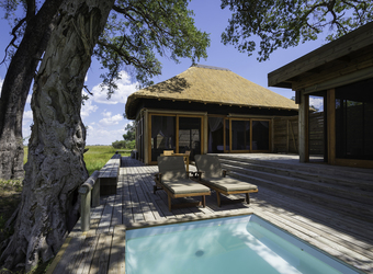 Vumbura Plains Camp, exquisite outdoor deck lounge area with welcoming light blue pool and viewing areas for wildlife sightings all around, Botswana