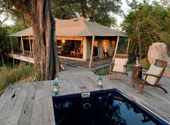 Zarafa Camp, beautiful master bedroom with huge bed and en suite bathroom with copper bath tub and fashionable furnishings, Botswana safaris, Africa