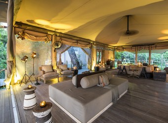 Duma Tau Camp, gorgeous screened main lounge area, surrounding windows on every side with views of the wilderness, golden lit canvas ceiling, Botswana