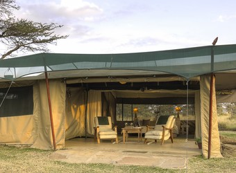 Kicheche Bush Camp, dining table set for dinner as an endiginous person brings lanterns to light up the meal along with the campfire, Kenya, Africa