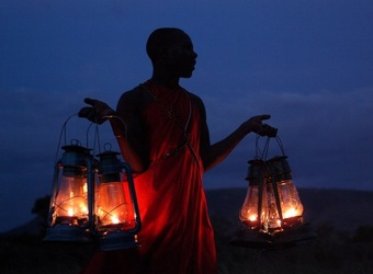 Kicheche Bush Camp, safari crew member holds a bunch of lanterns at his sides silouetted against the dark blue sky in Kenya, Africa safaris