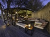 Khalahari Plains Camp, outdoor lounge area with overhanging tree, raised wooden platfom with comfotable couches, intimate lighting, Botswana, Africa