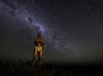 Khalahari Plains Camp, spectacular stars, local African native in traditional dress with a handmade bow and arrow, milky way, Botswana, Africa