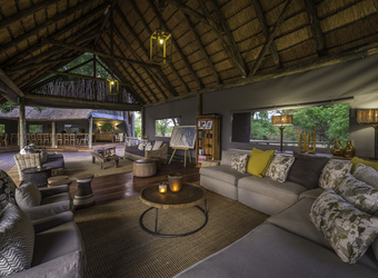 Seba Camp, large indoor lounge area immaculately decorated with modern furniture but with a rustic old safari feel in Botswana, Africa safari