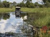 Seba Camp, a safari vehicle attempts to cross a large watering hole as it just begins its progress through the obstacle in Botswana, Africa safaris