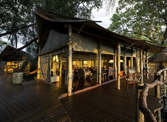 Tobu Tree Camp, large beautifully stained deck encircling enclosed lounge area at luxury safari camp, tented indoor/outdoor relaxation, Botswana