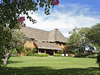 Lewa Wilderness Lodge, beautiful green lawn sloping up to the thatched roof of  the safari lodge, clear blue skies above and welcoming trees, Kenya