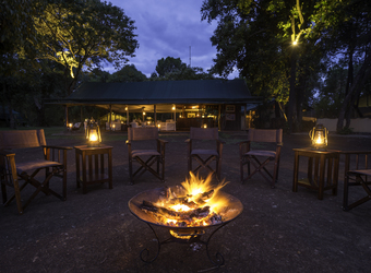Little Governor's Camp, a group of safari guests enjoys a drink and good conversation around the roar of the crackling fire in Kenya, Africa safaris