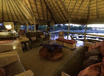 Savuti, luxury indoor lounge area with high vaulte wood panneled  ceilings and beautiful décor, microfiber couches and comfortable chairs abound