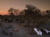 Chobe Under Canvas, mobile safari camp, private canvas-sided tents, expansive open area with fire and surrounding seating, sunset over Africa camp