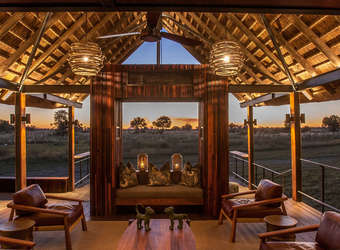 Chitabe Camp, thatched lounge with contemporary furniture, luxurious trappings with high vaulted celing, beautiful wood-panneled ceiling, Africa