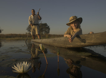 Chitabe camp, guided canoe river tour, grooved canoe, young child with water flowers, lily pads on the river, Okavango Delta, Botswana, Africa safari