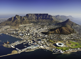 Overhead view of Cape Town and Table Mountain rising towards the heavens behind the buildings, picturesque places in South Africa