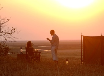 A pair of safari guests relax in comfortable chairs as the sun slowly begins its decent in the sky in Katavi National Park, Tanzania
