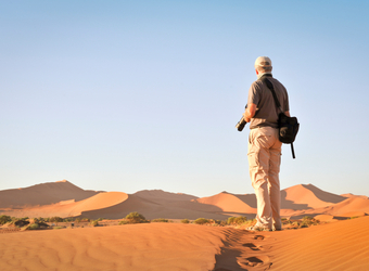 A visitor and photographer overlooks the vast sand dune plains looking for the right shot in Sossusvlei, Namibia