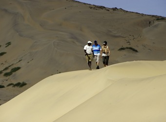 Three safari guests walk along the ridge of a massive beige colored sand dune in the Hartmann Valley, Namibia