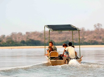 Safari guests motor along in a motorboat along the Rufiji River in search of animal sightings in the Selous Game Reserve, Tanzania