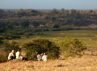 A group of tourists with guide view from a hilltop the surrounding wilderness of the Selous Game Reserve, Tanzania