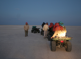 A group of safari tourists takes a night ATV ride through the Kalahari Desert wearing bandanas to prevent sand from getting in their faces