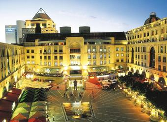 Gorgeously constructed building architecturally along with a nice plazza and a variety of cars and people in downtown Johannesburg, South Africa