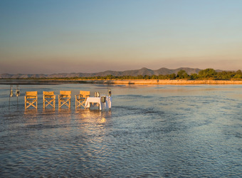 Picturesque dining setup in the shallows of the water with a view of the mountains and blue sky opening up behind in Lusaka, Zambia