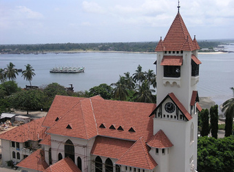 A nice sea view of the Indian Ocean with a beautiful white and red church in the foreground and a large boat in the ocean in Dar es Salaam, Tanzania