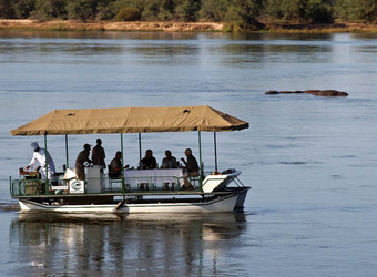 A safari boat filled with safari guests meanders down the Zambezi River while looking at submerged hippos in Lower Zambezi National Park, Zambia