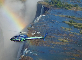 An overhead view of Victoria Falls from the air with a helicopter and a rainbow in the same shot, Zambia
