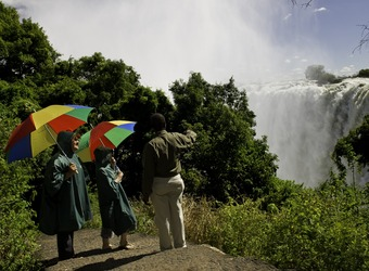 A guide informs on Victoria Falls to two tourists with vibrantly promary colored umbrellas wearing ponchos in Zimbabwe.