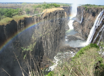 The multitudes of water cascade over Victoria Falls as a rainbow paints a stunning vista of the Zambezi Gorge in Zimbabwe