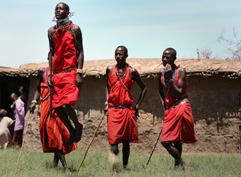 Local villagers and native peoples perform a traditional dance wearing traditional garb in Maasai Mara National Reserve, Kenya