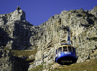 Blue and orange cable car ascends towards the top of Table Mountain with the deep blue sky visible in Cape Town, South Africa