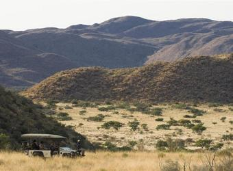 Safari vehicle surrounded by nothing but African wilderness in the form of plains, grasslands, and mountains in southern Kalahari, South Africa