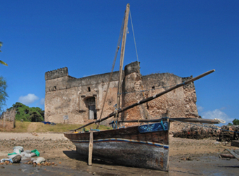 A traditionally made sailboat hauled ashore of the Indian Ocean with the ruins of an old house towering over the whole scene in Dar es Salaam, Tanzania