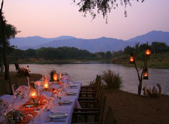 A gorgeous dining table is set out at twilight with lanters lighting the surrounding area with a view of the Zambezi River and mountains, Zambia