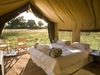 Chobe Under Canvas, comfortable canvas sided bedroom, open door and windows to nature with natural light slpilling in, foldable chairs with a view