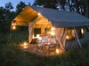 Chobe Under Canvas, secluded canvas sided tent lit up at twilight, comfortable folding chairs perched in front, contrast with surrounding wilderness