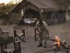 Chobe Under Canvas, canvas tent blended into nature, camp guide starting a fire with large tree branches, several comfortable folding chairs, Botswana