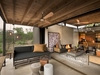 Lion Sands Ivory Lodge indoor outdoor living space pattern rug modern gray sofa exposed beams and shiplap ceiling
