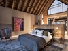 Lion Sands Ivory Lodge Jacana Suite gray and white color palette bedroom with vaulted ceiling exposed beams shiplap